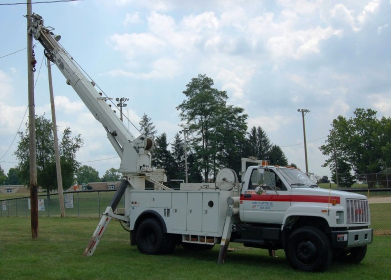 "Altec digger derrick truck equipped for wooden pole installations, augur holes up to 30"" diameter, lifting and placing materials up to 5,000 pounds, and winching large exterior wire pulls."